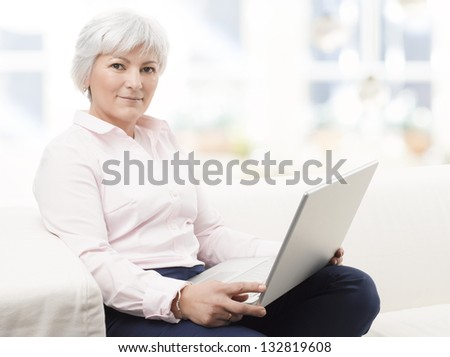 Portrait of a smiling senior woman working on laptop - stock photo