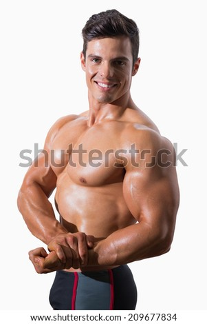 Portrait of a smiling shirtless muscular man over white background - stock photo
