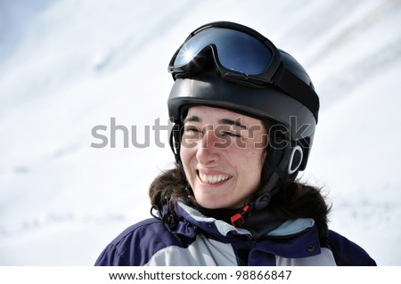Portrait of a smiling skier woman with helmet in the Alps