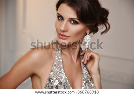 Portrait of a smiling smart dressed young beautiful woman in the elegant evening dress and expensive earrings jewelry with expressive make up - stock photo