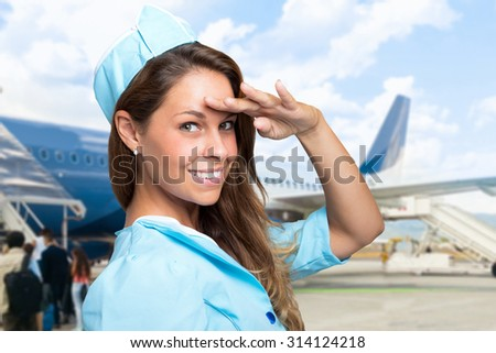 Portrait of a smiling stewardess in front of a plane - stock photo