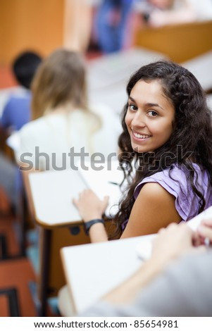 Portrait of a smiling student being distracted in an amphitheater - stock photo