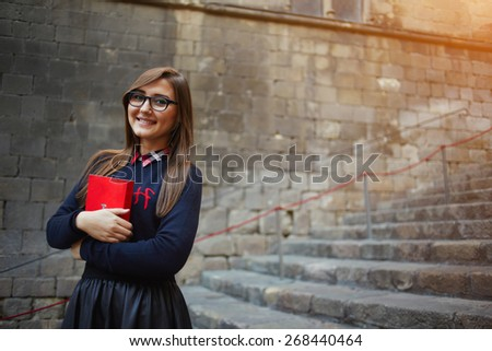 Portrait of a smiling student girl holding red book close to her chest standing on campus, attractive female student in glasses holding red bright book standing outdoors, flare light, filtered image - stock photo