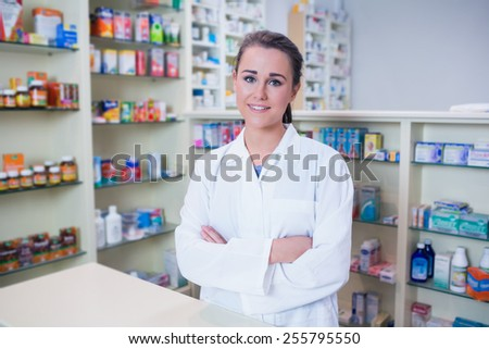 Portrait of a smiling student in lab coat looking at camera in the pharmacy