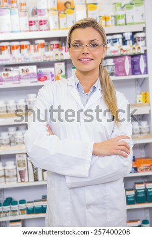 Portrait of a smiling student in lab coat with arms crossed in the pharmacy - stock photo