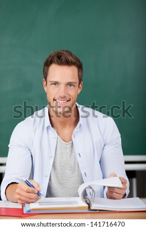 Portrait of a smiling student looking in camera with white binder in front of a green chalkboard