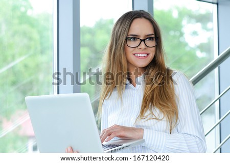 Portrait of a smiling successful businesswoman with computer - stock photo
