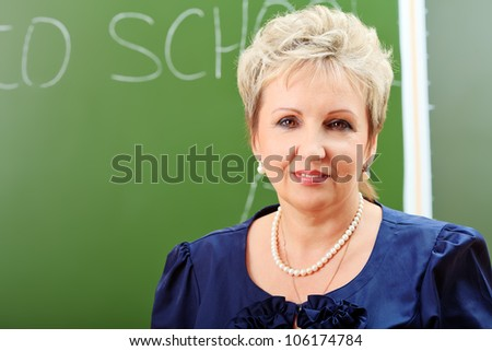Portrait of a smiling teacher in a classroom. - stock photo