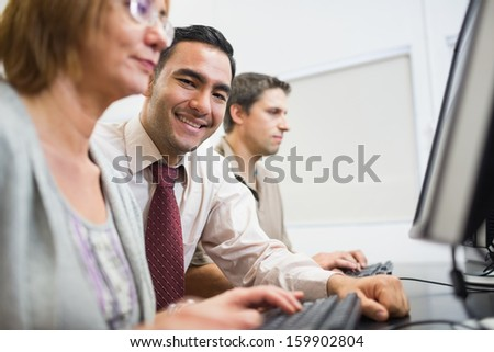 Portrait of a smiling teacher with mature students using computer in the computer room