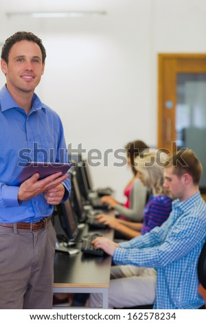 Portrait of a smiling teacher with young college students using computers in the computer room - stock photo