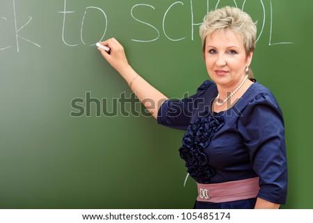 Portrait of a smiling teacher writing on a blackboard. - stock photo