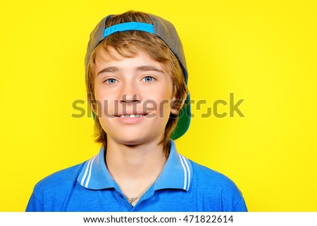 Portrait of a smiling teenage boy over yellow background. Studio shot. Teen fashion.