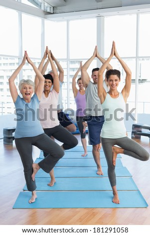 Portrait of a smiling trainer with class standing in tree pose at yoga class