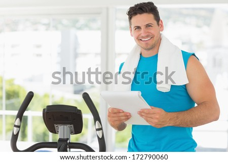 Portrait of a smiling trainer with clipboard standing in the gym - stock photo