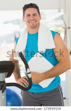 Portrait of a smiling trainer with clipboard standing in the gym