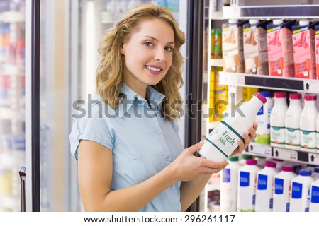 Portrait of a smiling woman having on her hands a milk bottle in supermarket