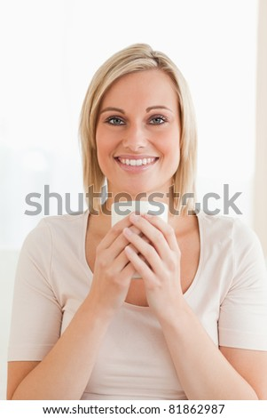 Portrait of a smiling woman holding a cup of coffee while looking at the camera