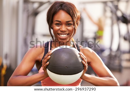 Portrait of a smiling woman holding a medicine ball at a gym - stock photo