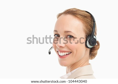 Portrait of a smiling woman in a suit with headset against white background