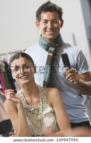 Portrait of a smiling woman in dressing room with male hair stylist - stock photo