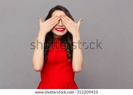 Portrait of a smiling woman in red dress covering her eyes over gray background - stock photo