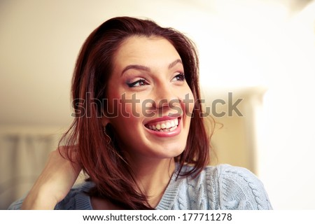 Portrait of a smiling woman looking away at home - stock photo