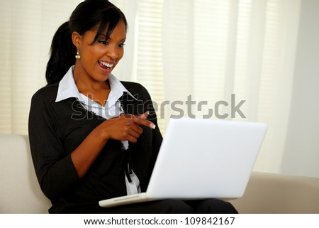 Portrait of a smiling woman on black suit pointing to laptop screen while sitting on sofa at home indoor