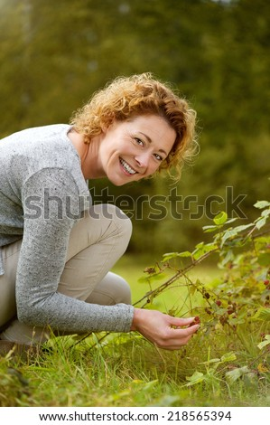 Portrait of a smiling woman picking berries in the forest - stock photo