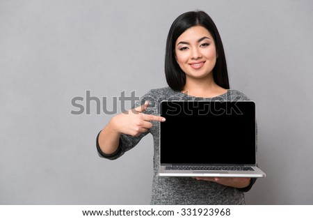 Portrait of a smiling woman pointing finger on blank laptop computer screen over gray background - stock photo