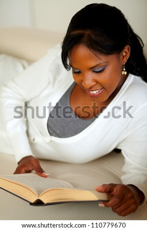 Portrait of a smiling woman reading a book while lying on couch at home indoor - stock photo