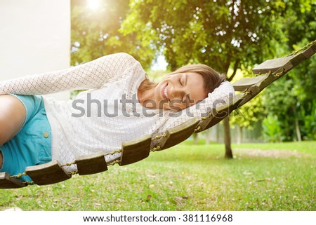 Portrait of a smiling woman relaxing on hammock  - stock photo