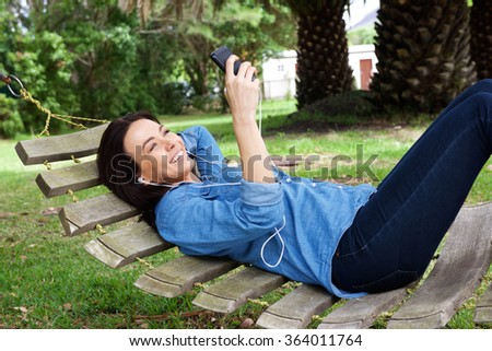Portrait of a smiling woman relaxing on hammock with mobile phone - stock photo