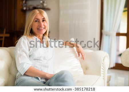 Portrait of a smiling woman relaxing on the couch in her home