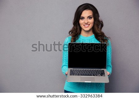 Portrait of a smiling woman showing blank laptop computer screen over gray background - stock photo