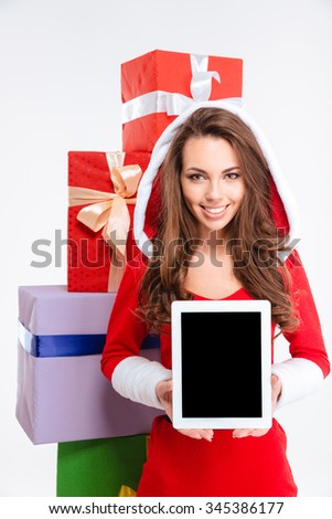 Portrait of a smiling woman showing blank tablet computer screen with gift boxes on background