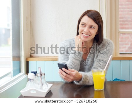 Portrait of a smiling woman sitting at with mobile phone