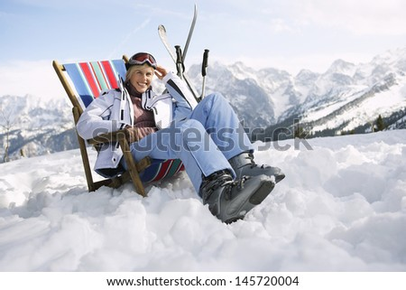 Portrait of a smiling woman sitting on deckchair in snowy mountains - stock photo