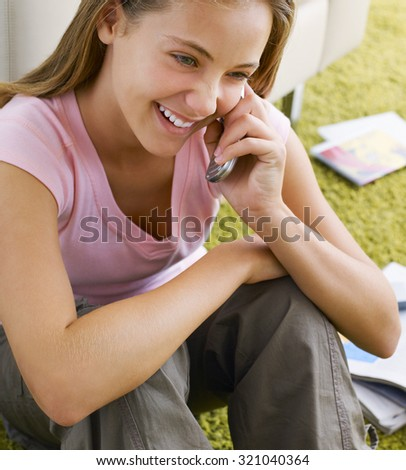 Portrait of a smiling woman sitting on the floor and talking on the phone - stock photo