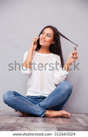Portrait of a smiling woman sitting on the floor and talking on the phone on gray background - stock photo