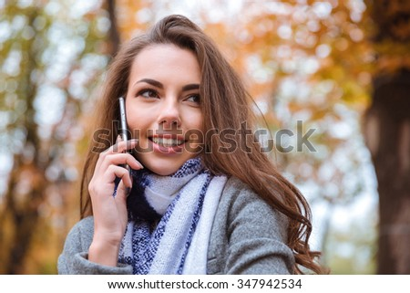 Portrait of a smiling woman talking on the phone in autumn park - stock photo