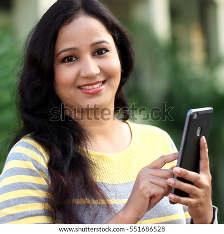 Portrait of a smiling woman texting with her cellphone