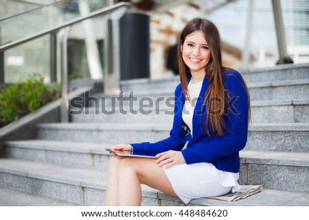 Portrait of a smiling woman using a digital tablet - stock photo