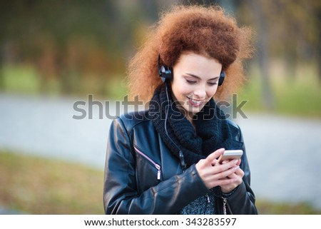 Portrait of a smiling woman using smartphone with headphones outdoors
