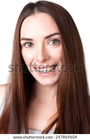 portrait of a smiling woman wearing braces. Isolated. White background. - stock photo