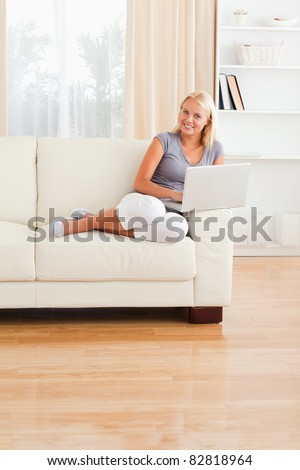 Portrait of a smiling woman with a laptop in her living room - stock photo
