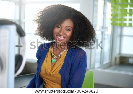 Portrait of a smiling woman with an afro at the computer in bright glass office - stock photo