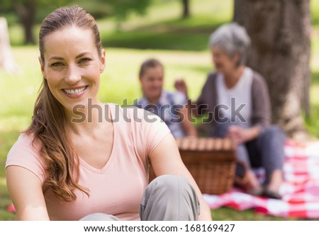 Portrait of a smiling woman with grandmother and granddaughter in background at the park
