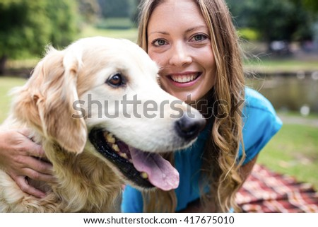 Portrait of a smiling woman with her pet dog in park
