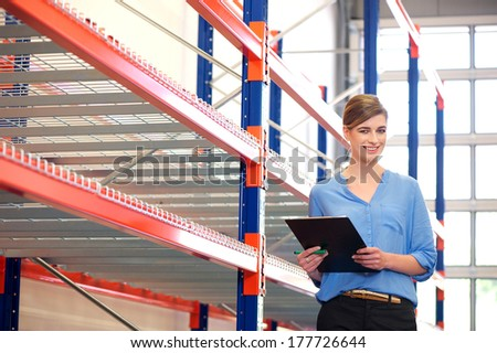 Portrait of a smiling woman working in warehouse - stock photo