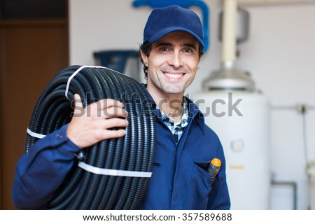 Portrait of a smiling worker carrying corrugated conduit - stock photo